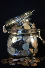 Coins in a glass jar on a black background