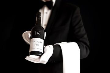 Waiter in tuxedo holding a bottel of red wine