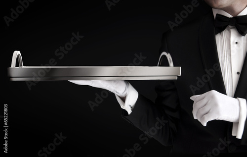 Staande foto Assortiment Waiter in tuxedo holding an empty tray isolated on black