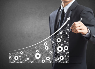 Business man drawing growing economy and industry by gears
