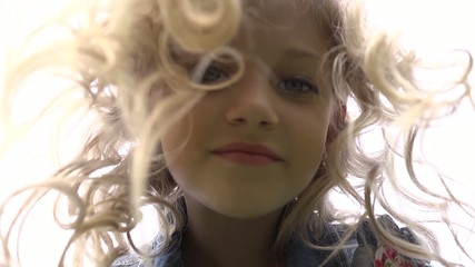 Face of a little girl with ringlets of hair falling down