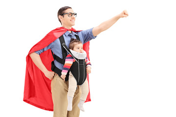Male superhero with raised fist carrying a baby