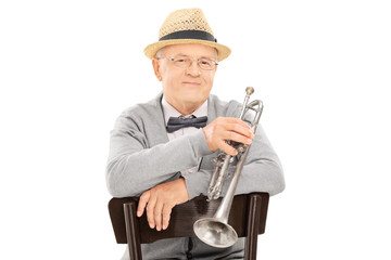 Senior gentleman holding trumpet seated on chair