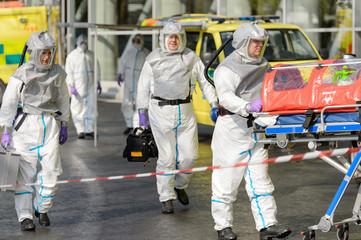 Biohazard team with stretcher walking on street