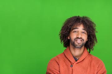 lächelnder mann steht vor grüner wand