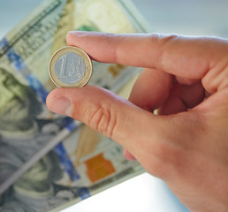 hand with dollars and euro coin
