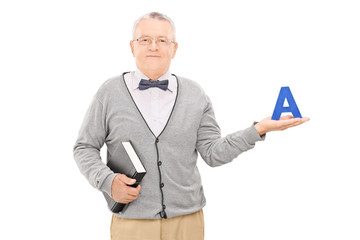 Male teacher holding book and the letter a