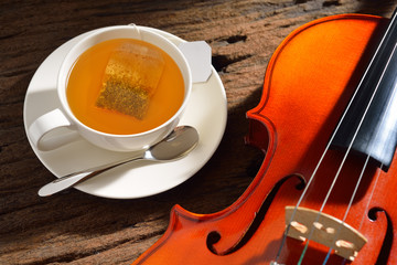 Cup of tea with tea bag and violin on wooden table