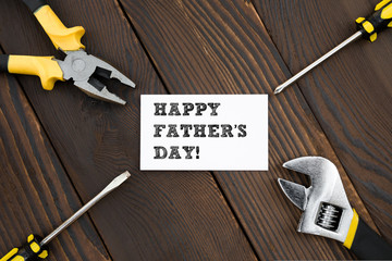 card of HAPPY FATHER'S DAY and tools on wood