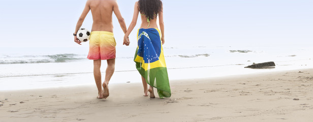 young couple walking along beach with brazil flag and football