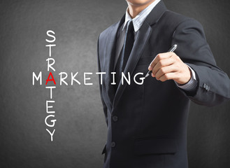 Business man writing marketing strategy concept by crossword