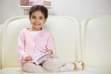 Cute smiling hispanic girl reading book