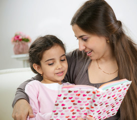 Cute little girl reading book with mother