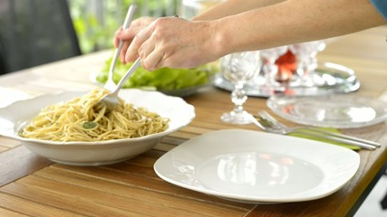 Woman Serving spaghetti with pesto sauce on plate