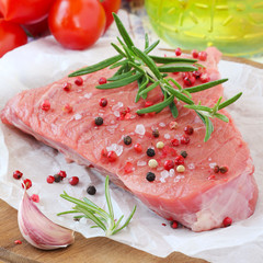 Raw beef steak with pepper beans, salt and fresh rosemary
