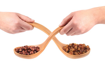 Collage of two spoons with nuts and raisins.