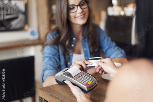 Smiling woman paying for coffee by credit card - 65235266