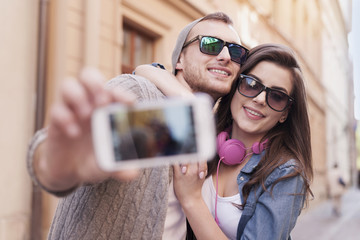 Loving couple taking selfie in the city