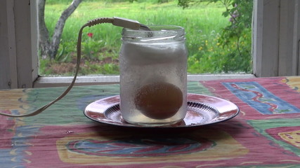 tourist boiling egg with  vintage heating coil in glass jar