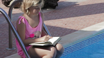 Blonde child girl reading a book on a swimming pool
