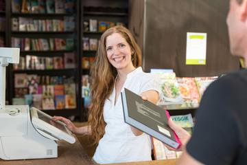 Kassiererin in einer Buchhandlung verkauft einem Kunden ein Buch