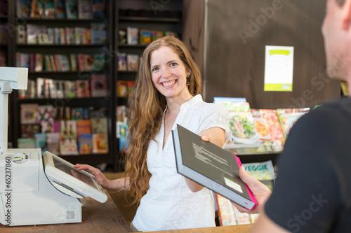Kassiererin in einer Buchhandlung verkauft einem Kunden ein Buch - 65237868