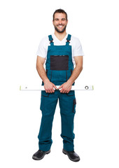 Smiling worker in green uniform with spirit level