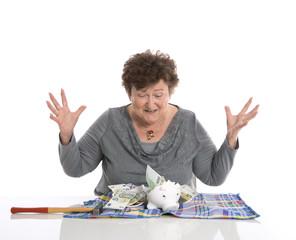 Glückliche lachende Rentnerin mit Geld vom Sparschwein