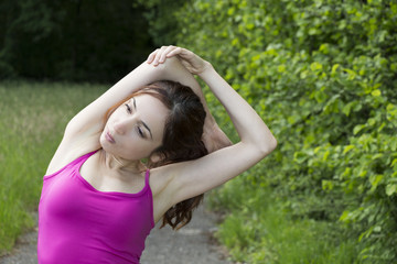 Young sporty woman stretching her arms outdoors