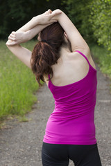 Rear view of a woman stretching outdoors
