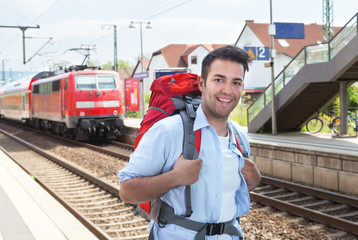 Lachender Tourist am Bahnhof mit Zug