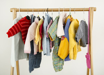 Wardrobe of newborn with clothes arranged on hangers toys