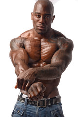 Topless black bodybuilder holding his hands like he surrender