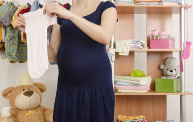 Pregnant woman shopping for clothes for her newborn baby