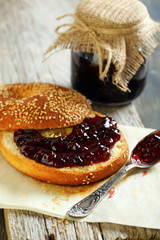 Homemade bagel with jam and tea spoon.