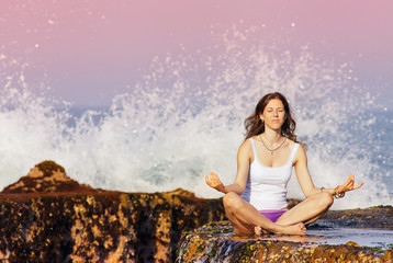 woman meditating in a yoga pose on a rock. Indonesia, Bali