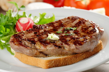 Grilled steak on toast bread, served with onion and vegetable