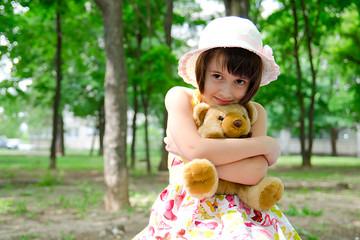 little girl with favorite teddy bear in  park