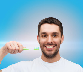 smiling young man with toothbrush