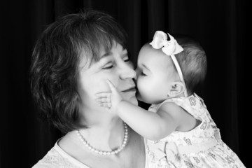 Baby granddaughter giving grandmother a kiss on the cheek