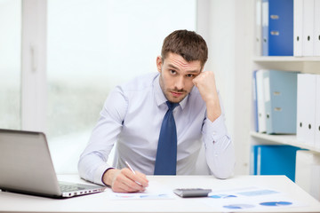 stressed businessman with laptop and documents