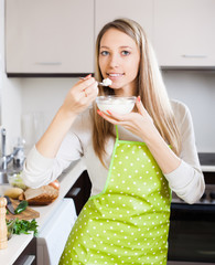 Smiling woman eating cottage cheese