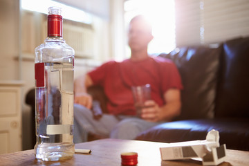 Man Sitting On Sofa With Bottle Of Vodka And Cigarettes