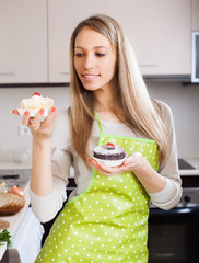 Blonde woman in apron with cakes