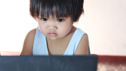Asian baby looking computer at home