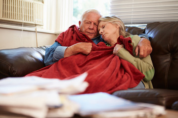 Senior Couple Trying To Keep Warm Under Blanket At Home