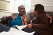 Worried Senior Couple Sitting On Sofa Looking At Bills