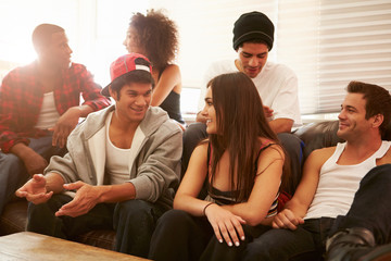 Group Of Young People Sitting On Sofa And Talking
