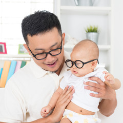 Young father and child with nerd glasses. Asian family at home.