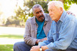 Man Comforting Unhappy Senior Friend Outdoors